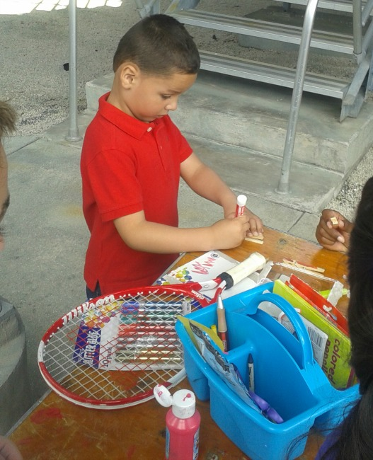 Joaquin making a clothespin creature at Delray Beach Open Kidz Day